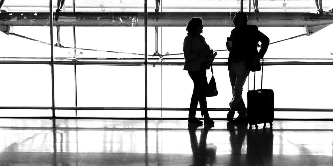 Zaseknutá rukojeť zavazadla - Dvě siluety lidí vedle sebe se zavazadly